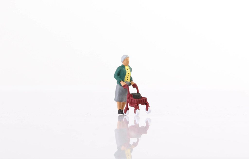Old miniature women on white background