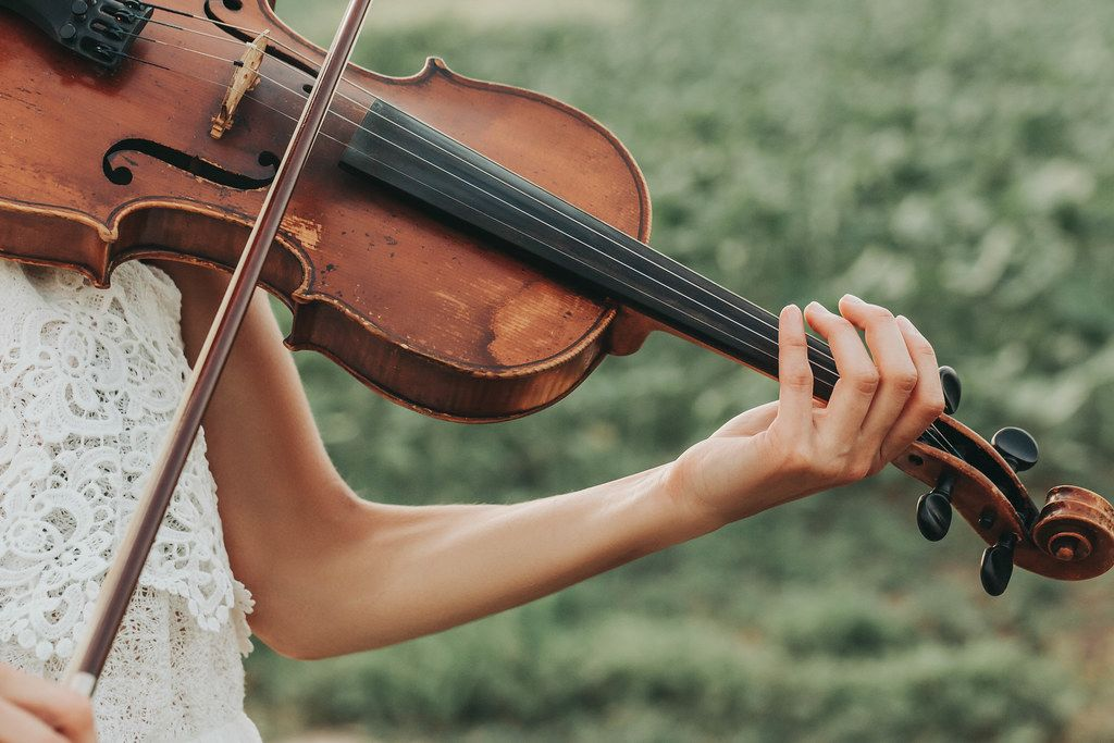 Old violin in the tender female hands of a playing violinist