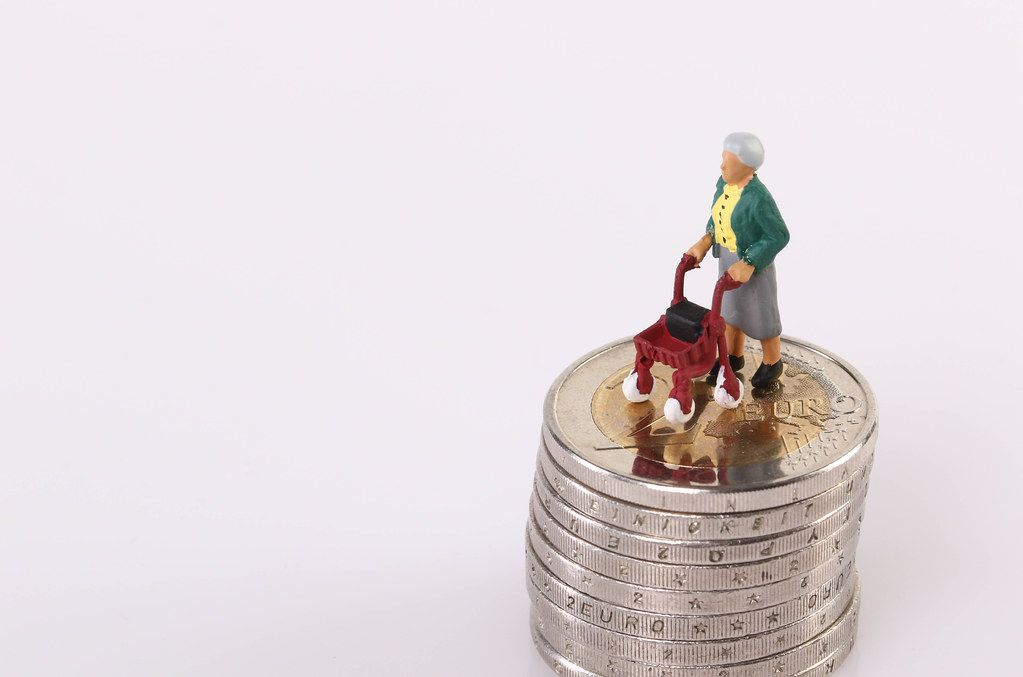 Old women standing on top of stack of coins on white background