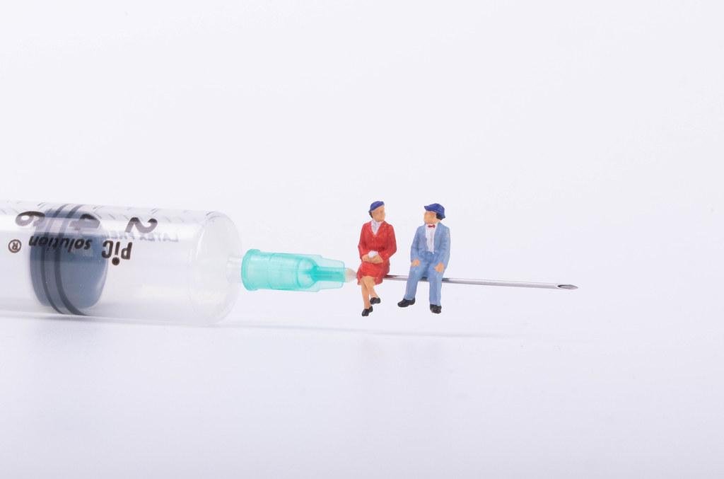 Older couple sitting on a syringe