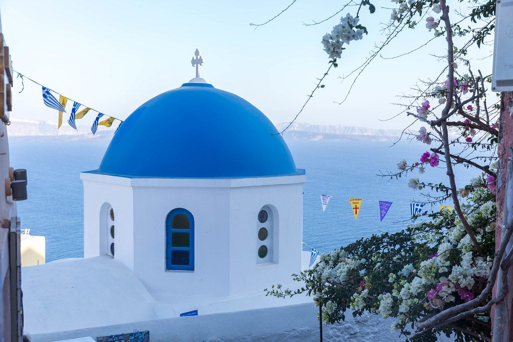 One of the famous blue domes in the picturesque village of Oia in Santorini with sea in the background