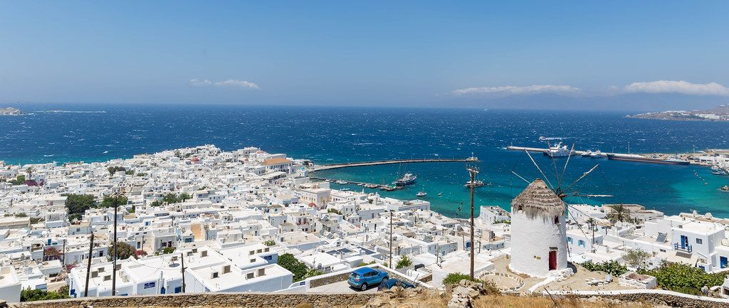 One of the landmark windmills of Mykonos and view of the city and port of Chora. Panoramic image