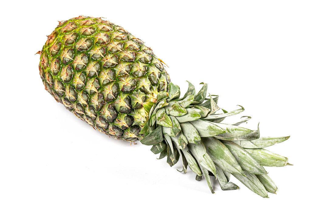 One whole pineapple with green leaves on white background