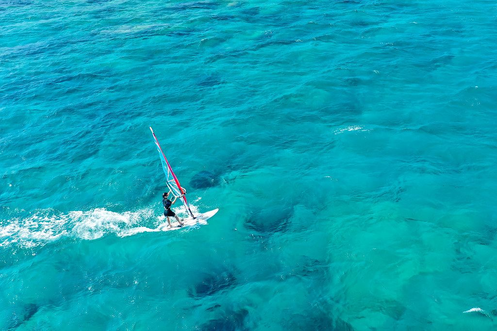 One windsurfer in the blue sea waters of Mikri Vigla, windsurf spot on the island of Naxos, Greece