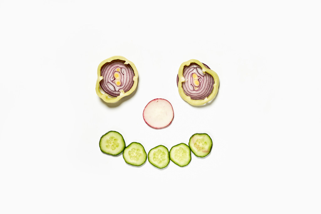 Onion rings and cucumber cuts making a smiling face