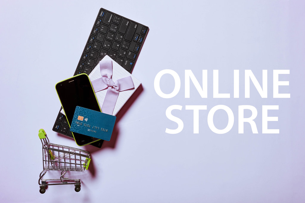 Online store - Shopping cart full with different items - computer keyboard, smartphone, gift box and credit card