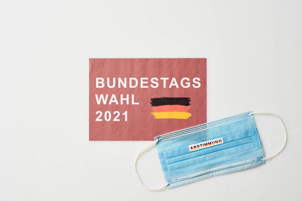 """OP-Maske mit Schrift """"Abstimmung"""". Roter Zettel mit deutscher Flagge und Schrift """"Bundestagswahl 2021"""""""