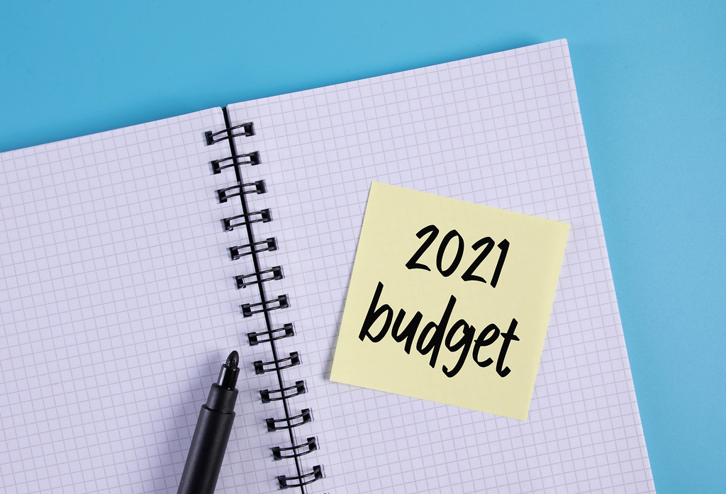 Open notebook and yellow sticky note with 2021 Budget text
