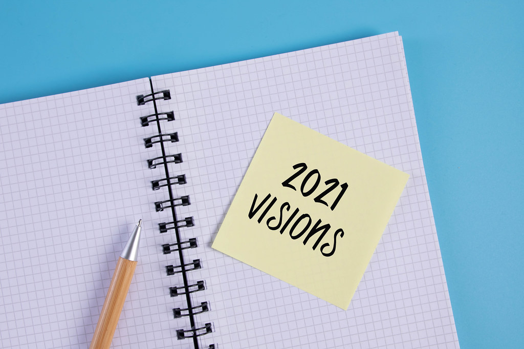Open notebook and yellow sticky note with 2021 Visions text