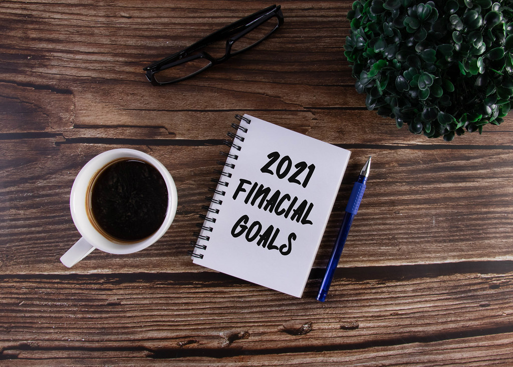 Open notebook with 2021 Financial Goals text on wooden table