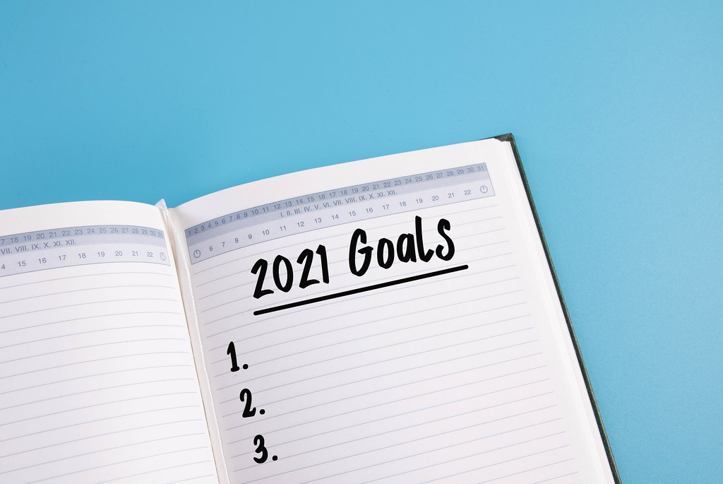Open notebook with 2021 Goals text on blue background