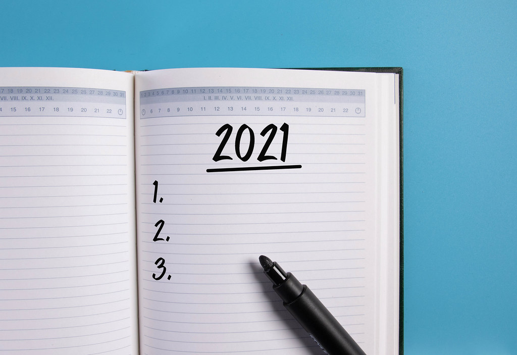 Open notebook with 2021 list on blue background