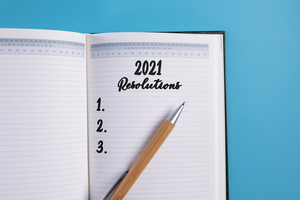 Open notebook with 2021 Resolutions list on blue background