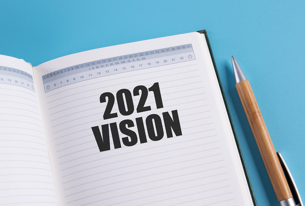 Open notebook with 2021 Vision text on blue background
