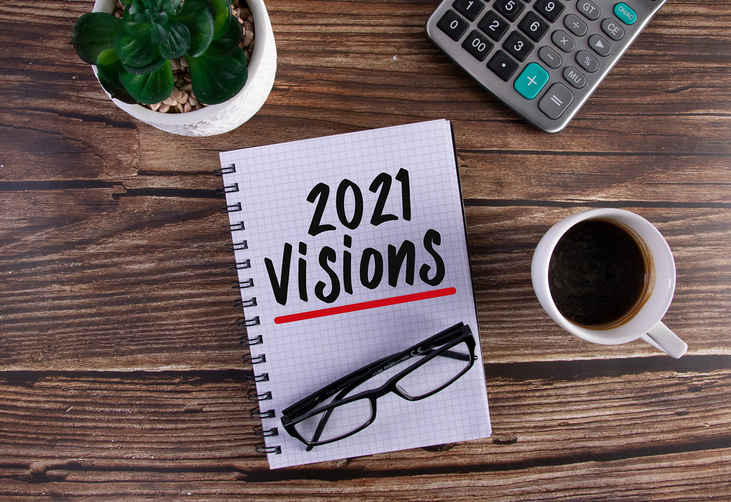 Open notebook with 2021 Visions text on wooden table