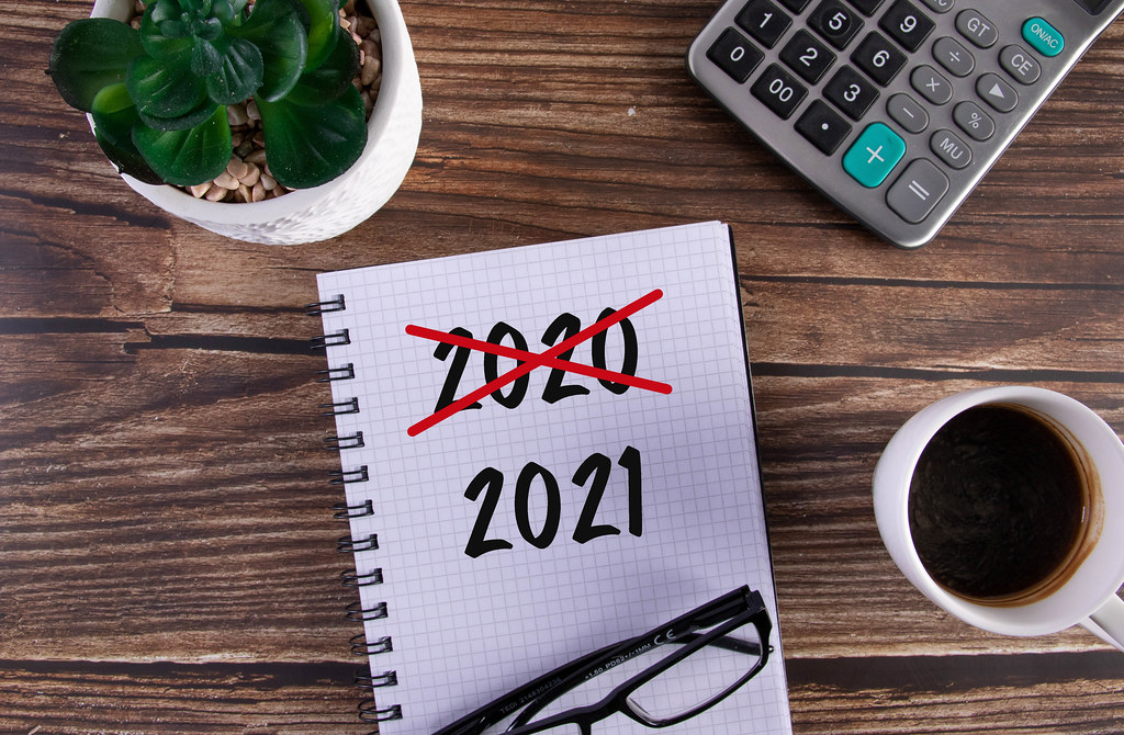 Open notebook with crossed 2020 text and 2021 text on wooden table