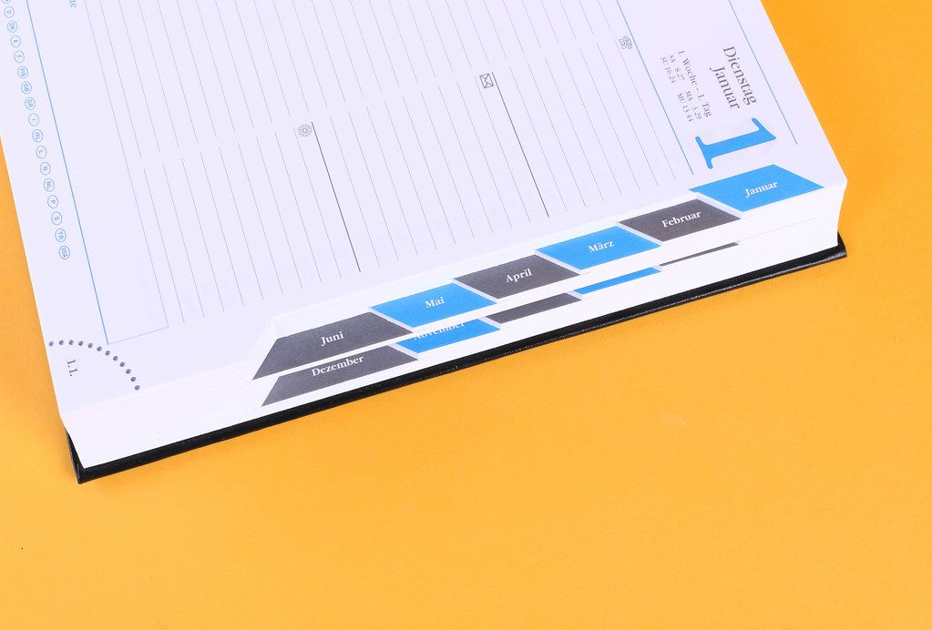 Open notebook with months list on orange background