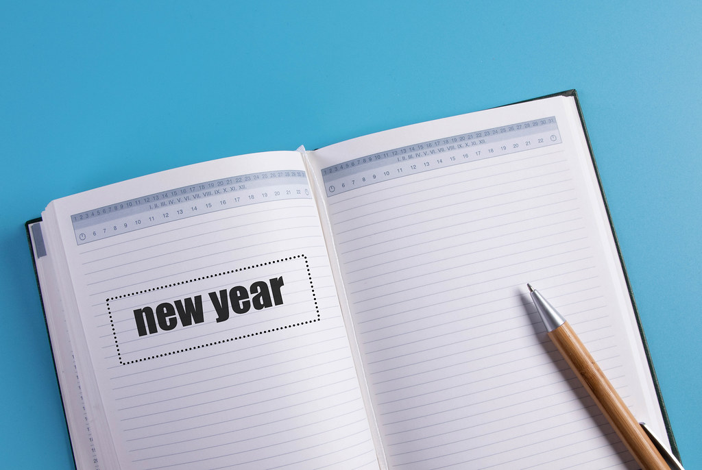 Open notebook with New year text on blue background