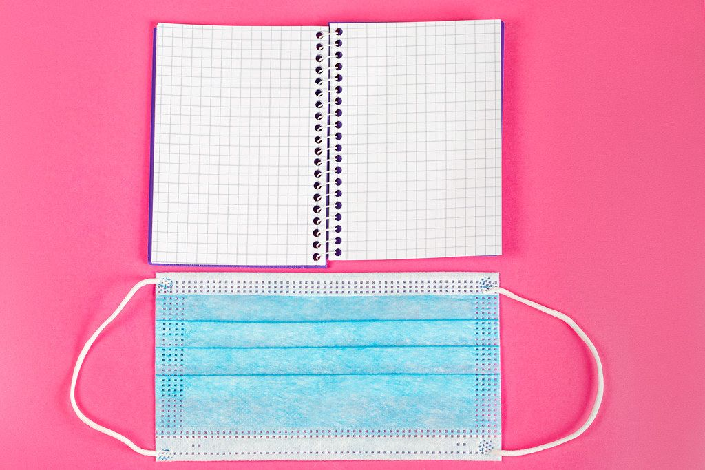Open notepad and medical mask on pink background, top view