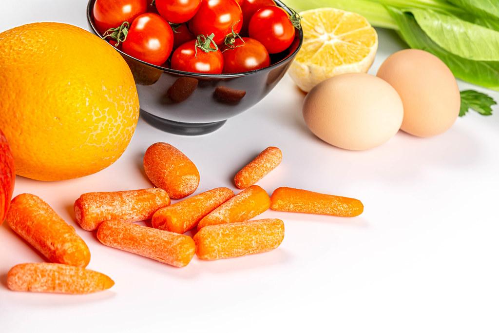 Orange, cherry tomatoes, carrots, pak choy cabbage, lemon and eggs on white