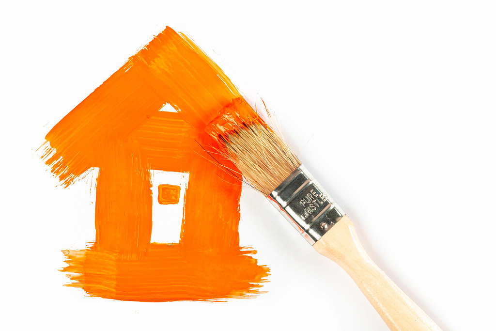 Orange painted house with brush, renovation concept