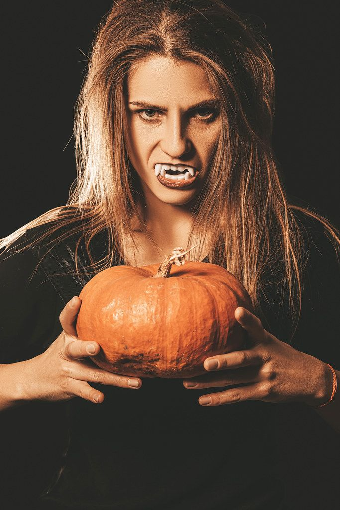 Orange pumpkin in the hands of a vampire woman on dark
