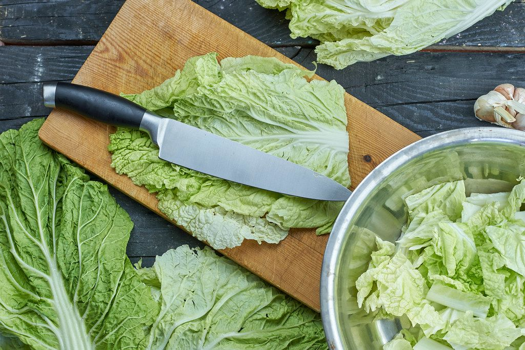 Organic fresh cabbage slices on the cutting board with a knife