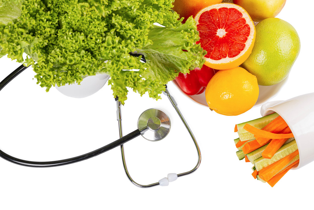Organic fresh fruits and vegetables with stethoscope on white background