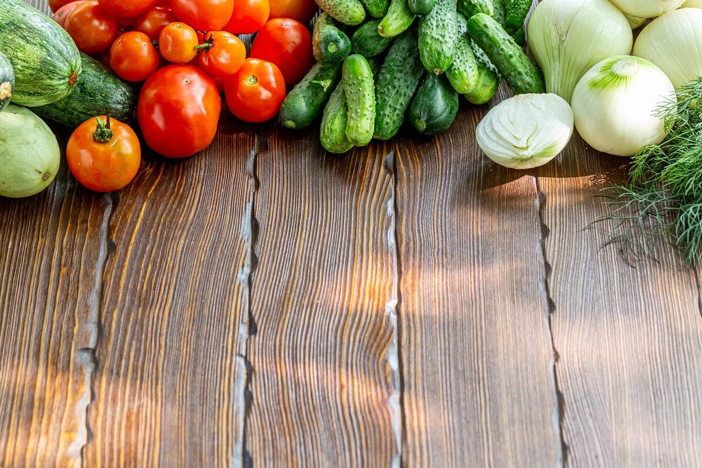 Organic raw vegetables on wooden background
