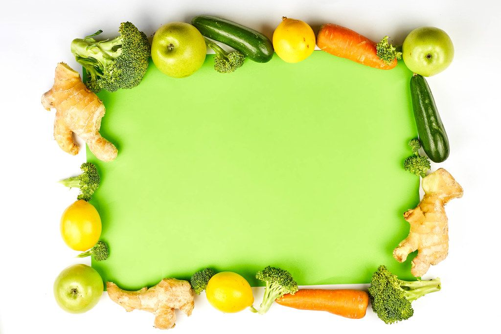 Organic vegetables and fruits frame on green background with copy space