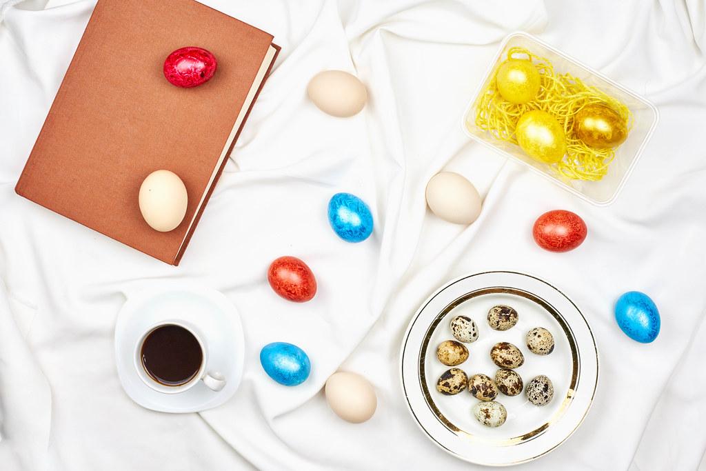 Ostern Hintergrund: gefärbte Eier, Wachteleier, Teller und Kaffeetasse und ein Buch auf weißem Bettlaken