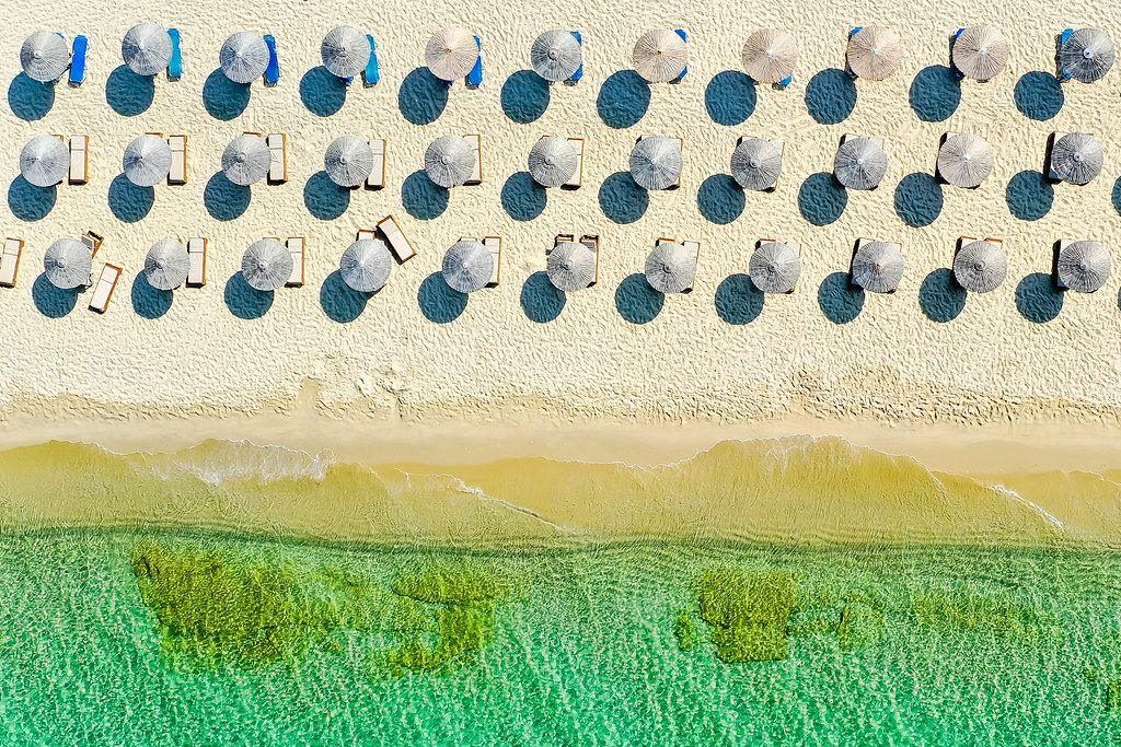Overhead aerial shot of three rows of thatched parasols with sunbeds on an empty beach in Greece