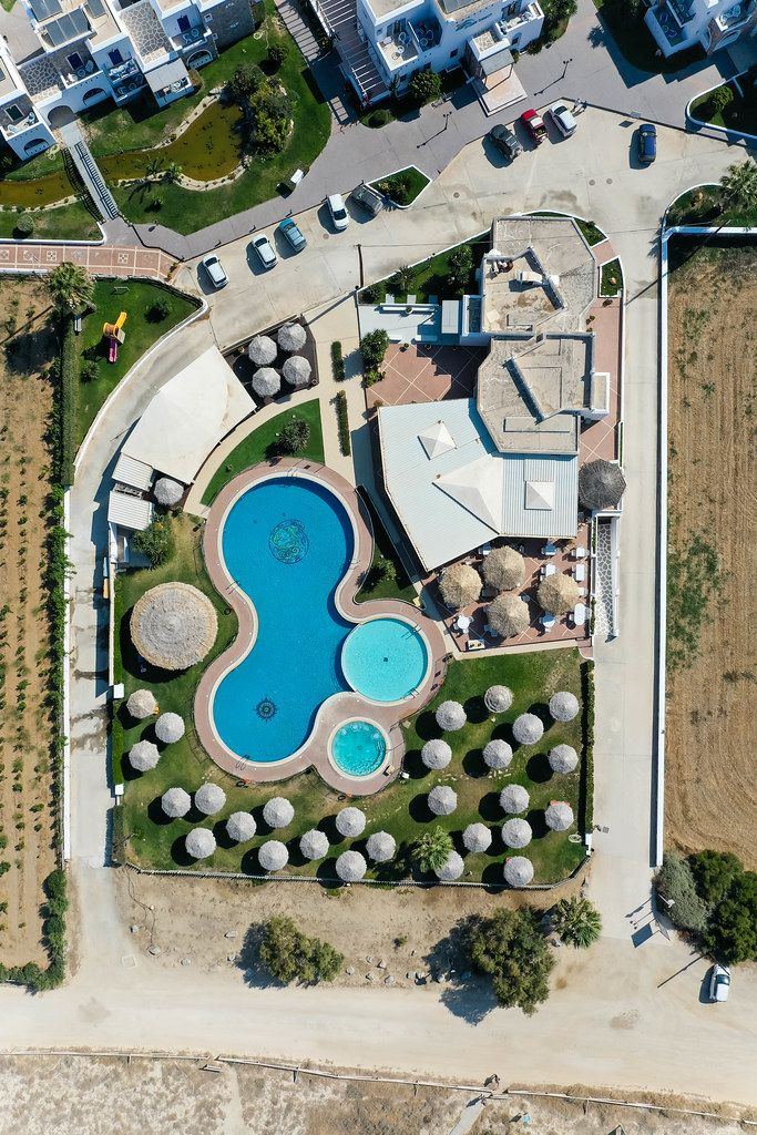 Overhead aerial shot of villa with large swimming pool and round parasols in Naxos, Cyclades, Greece