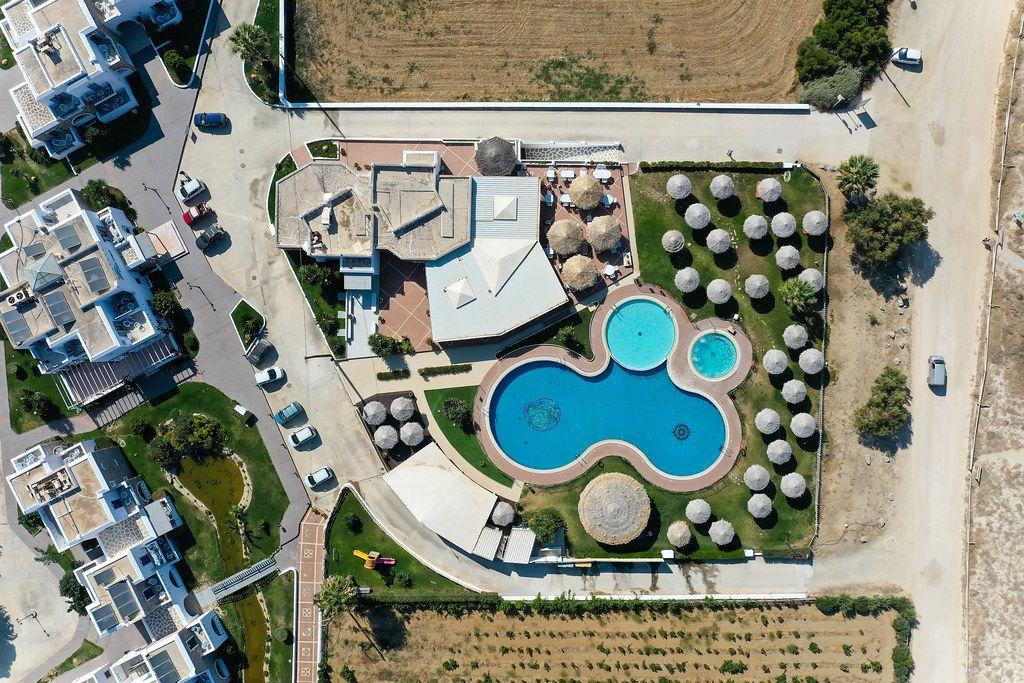 Overhead Drohnenaufnahme: Villa mit Schwimmbad und runden Sonnenschirmen auf Naxos, Zykladen