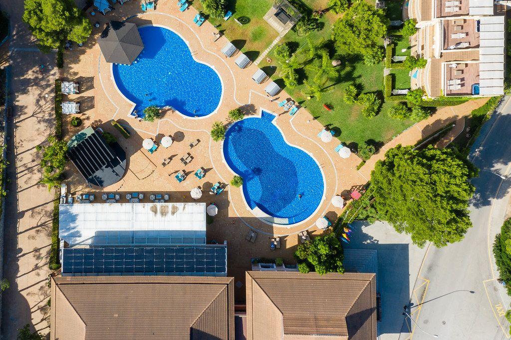 Overhead Drohnenaufnahme von zwei Pools in Achtform bei Cala Mesquida, Mallorca