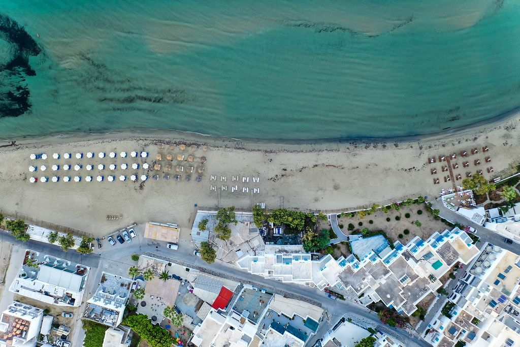Overhead drone shot of the Agios Georgios (Saint George) beach of Chora, Naxos, with shallow waters