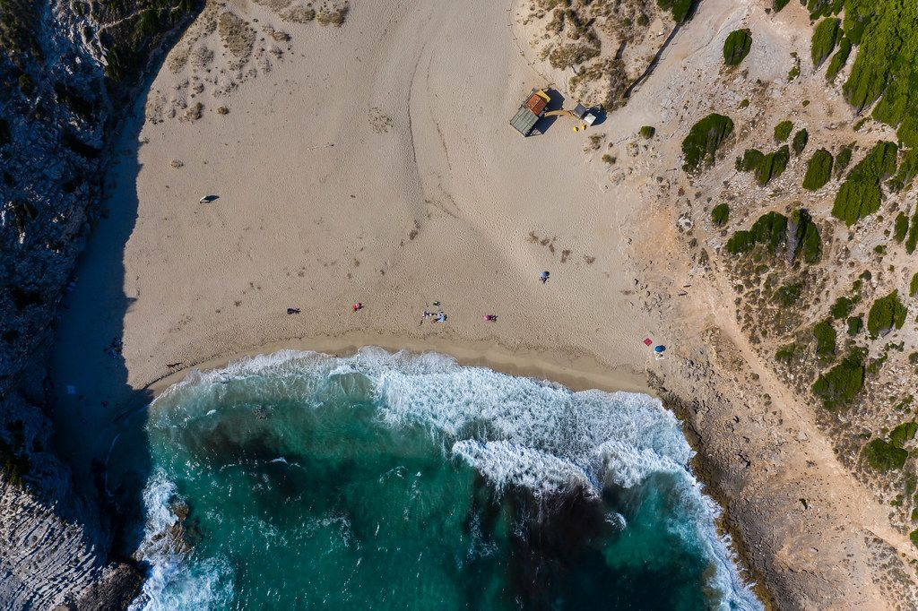 Overhead drone shot of waves hitting the shore at Cala Torta beach, north-east coast of Mallorca