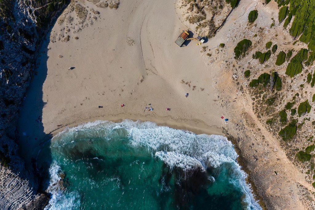 Overhead drone shot of waves hitting the shore at Cala Torta beach, north-east coast of Mallorca