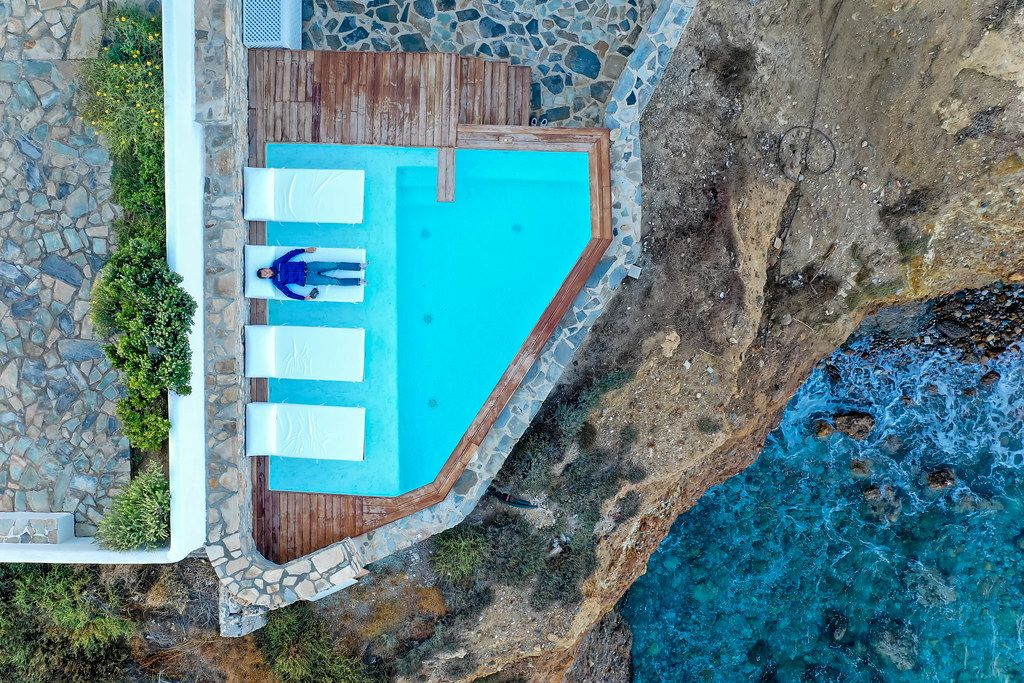 Overhead drone shot taken while relaxing by the pool with cliff and sea view. Iliada Suites hotel, Naxos