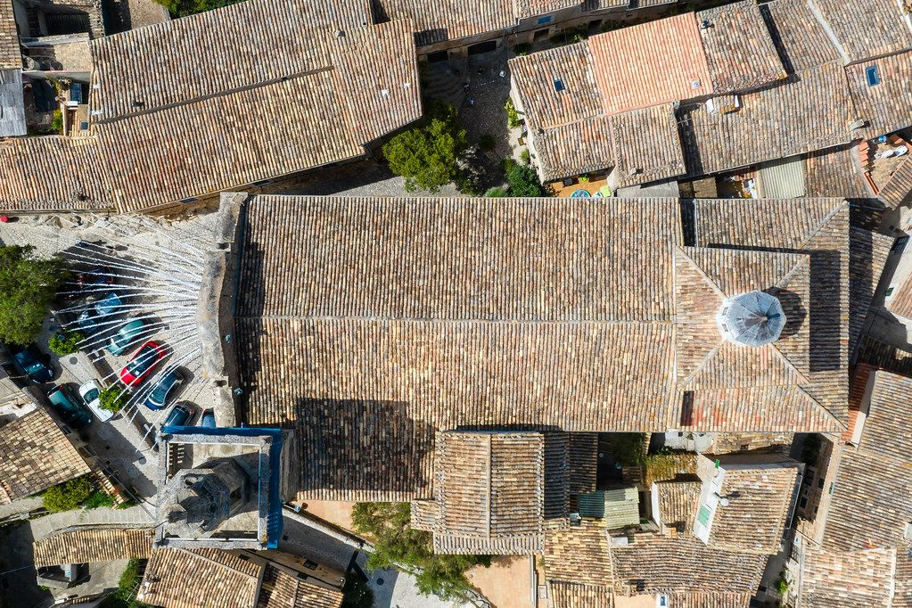 Overhead drone shot: the roof and bell tower of the parròquia de Sant Bartomeu church, Valldemossa