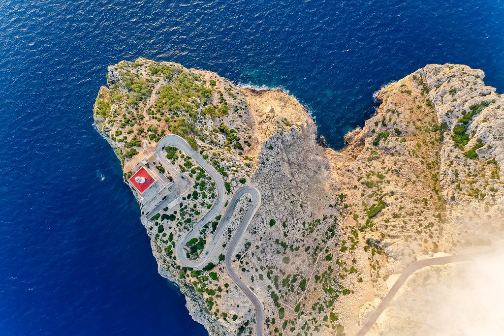 Overhead drone shot: the steep cliffs, rugged landscape and lighthouse of Cap de Formentor