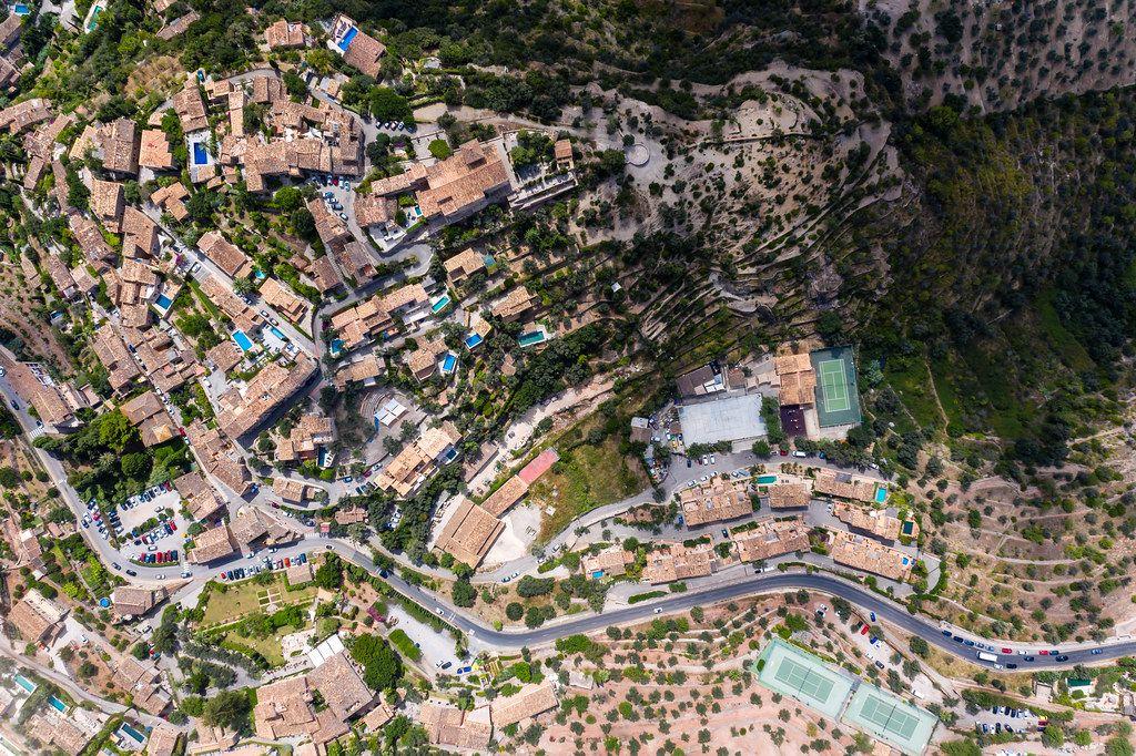 Overhead-Luftaufnahme der Dächer von Deià auf Mallorca. Häuser mit Pool mitten im Grünen