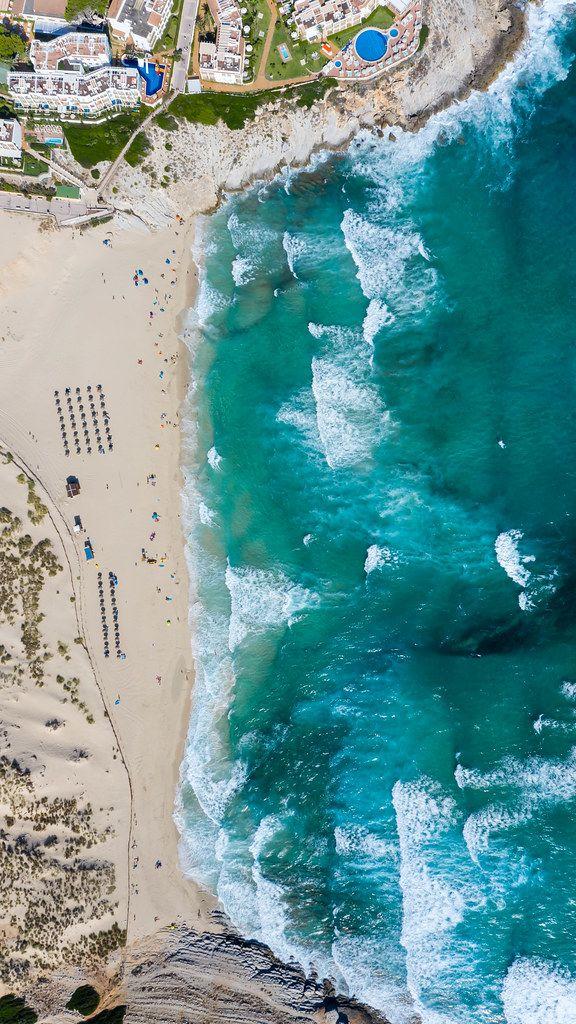 Overhead-Luftaufnahme vom langen Strand und Bucht von Cala Mesquida mit Wellen und Dünen