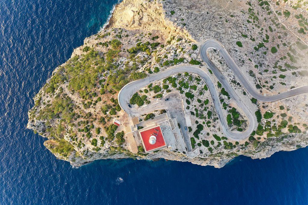 Overhead Luftbild: der weiß-rote Leuchtturm vom Cap de Formentor, die Steilküste und das blaue Meer