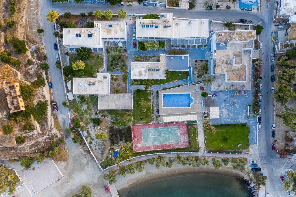Overhead Perspektive von Hotels, Schwimmbad, Tennisplatz, Strand auf der griechischen Insel Milos