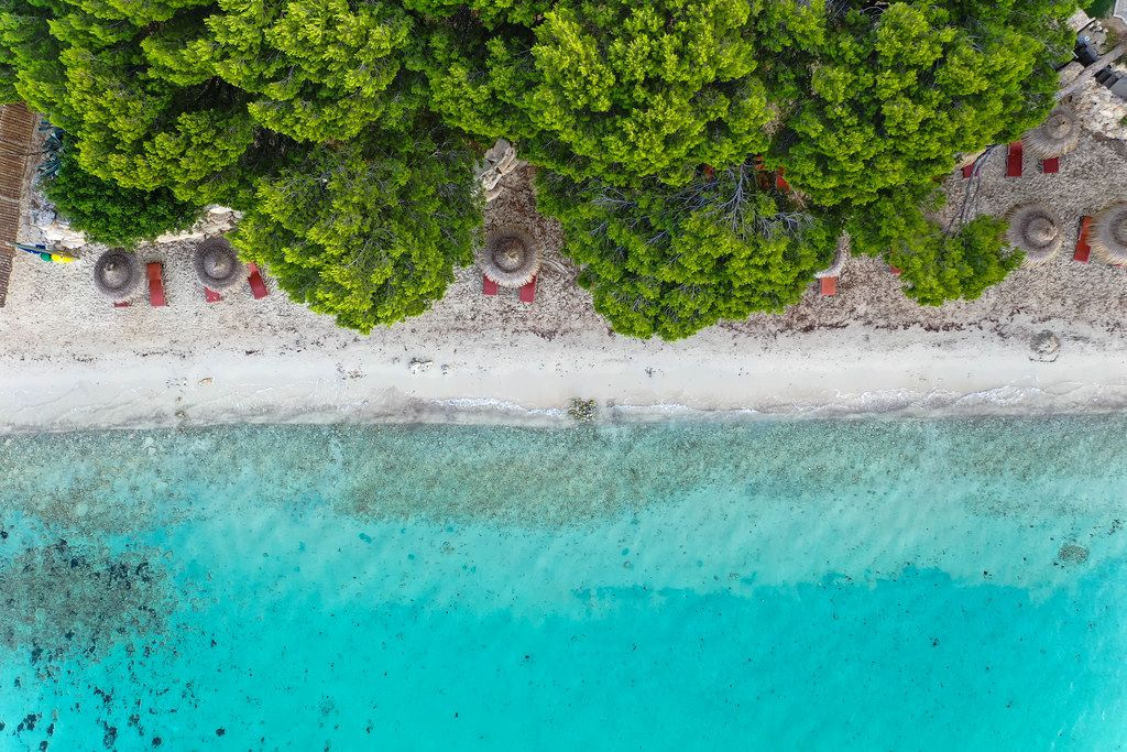 Overhead shot: Playa de Formentor on Mallorca with reddish-brown sun beds and straw parasols