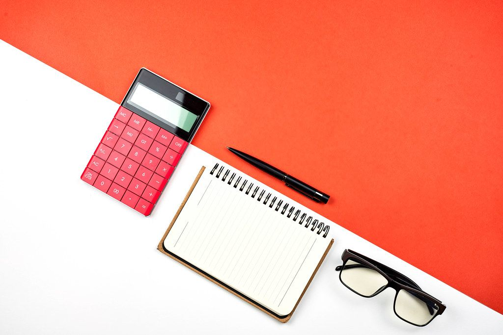 Overhead view of calculator, notepad and eyeglasses