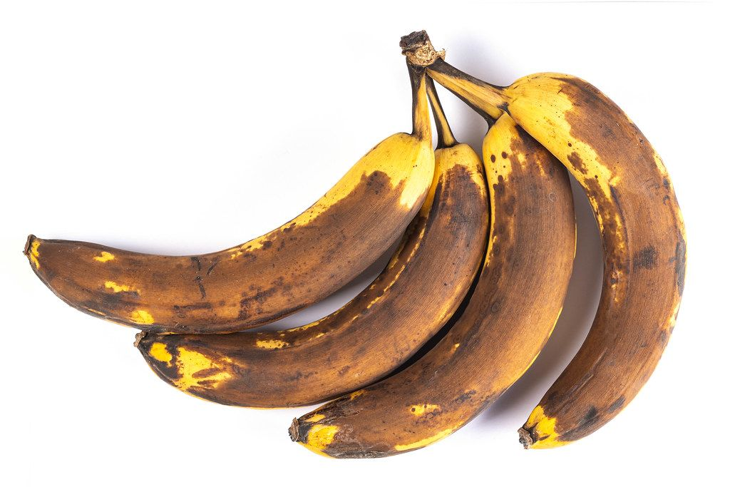 Overripe bananas on a white background, top view
