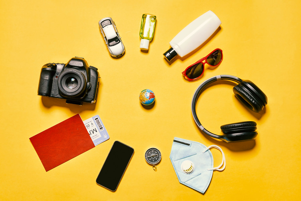 Packing backpack for a trip concept with traveler items on yellow background