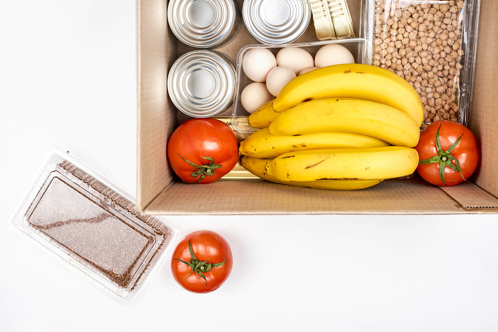 Packing basic food in a box as donation for those in need: tomatoes, bananas, eggs, nuts and tin cans